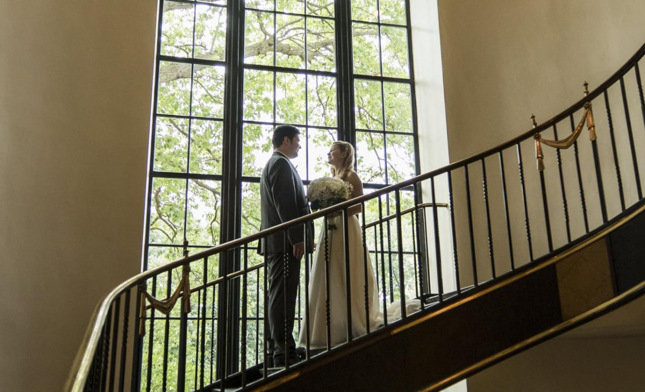 Couple posed on staircase beneath chandelier during wedding at faculty club